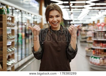 Photo of smiling young lady in supermarket standing and pointing to copyspace. Looking at camera.