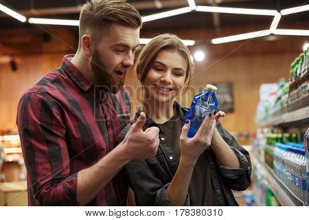 Image of young smiling loving couple in supermarket choosing water. Looking aside. Man showing thumbs up gesture.