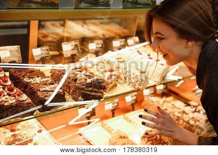 Image of cheerful young woman standing in supermarket choosing sweeties. Looking aside.