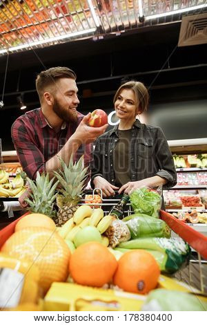 Image of cheerful young loving couple in supermarket with shopping trolley choosing fruits. Looking aside.