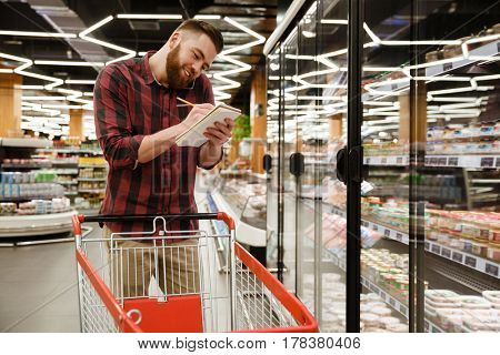 Image of smiling young man standing in supermarket choosing products while talking by phone and writing notes at notebook. Looking aside.