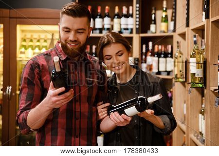 Image of young smiling loving couple in supermarket choosing alcohol. Looking aside.
