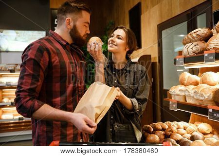 Photo of young happy loving couple in supermarket choosing pastries. Looking aside.