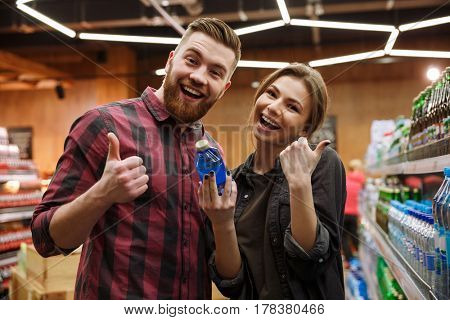 Photo of young happy loving couple in supermarket choosing water. Looking at camera. Showing thumbs up gesture.