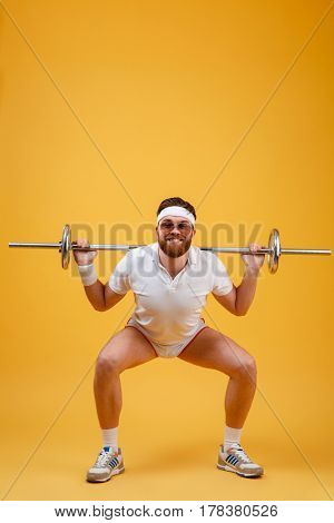 Photo of happy young sportsman wearing glasses make sport exercises with barbell isolated over yellow background. Looking at camera.