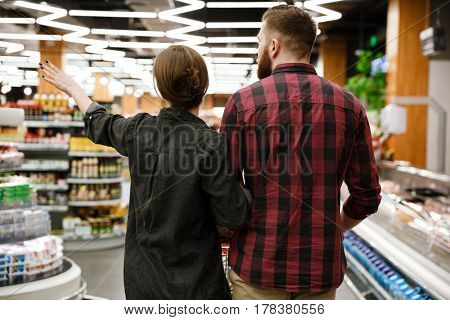 Back view image of concentrated young loving couple standing in supermarket choosing products.