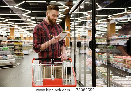 Image of happy young man standing in supermarket choosing products while reading notes at notebook. Looking aside.
