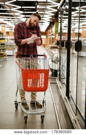 Photo of concentrated young man standing in supermarket choosing products while talking by phone and writing notes at notebook. Looking aside.