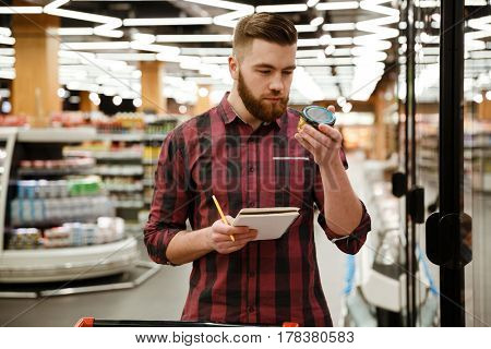 Image of positive young man standing in supermarket choosing products while reading notes at notebook. Looking aside.