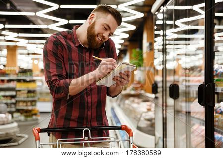 Photo of happy young man standing in supermarket choosing products while talking by phone and writing notes at notebook. Looking aside.