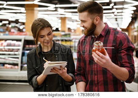 Image of happy young loving couple standing in supermarket choosing products while reading notes at notebook. Looking aside.