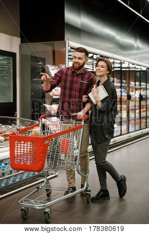 Image of young smiling loving couple in supermarket choosing products. Looking aside.