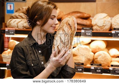 Image of young happy woman in supermarket choosing and smells pastries. Eyes closed.