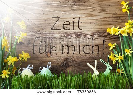 Wooden Background With German Text Zeit Fuer Mich Means Time For Me. Easter Decoration Like Easter Eggs And Easter Bunny. Sunny Yellow Spring Flower Narcisssus With Gras. Card For Seasons Greetings