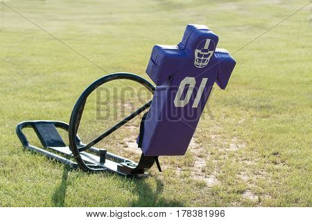 Purple tackling dummy sled in a grass field