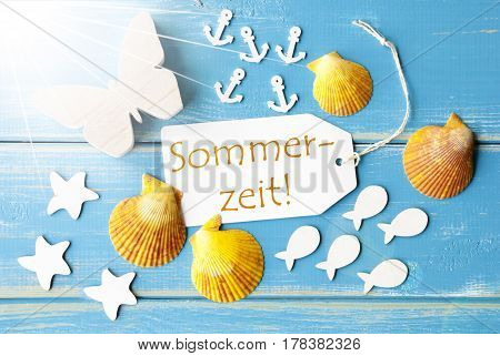 Flat Lay View Of Label With German Text Sommerzeit Means Summertime. Sunny Summer Greeting Card. Butterfly, Shells And Fishes On Blue Wooden Background