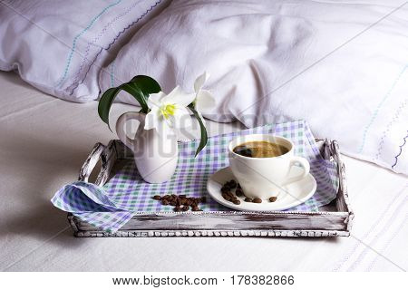 Cup of fresh coffee with white lily flowers in vase on rustic wooden serving tray. Tender love concept.