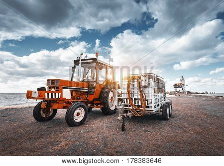 Red Tractor With Trailer Against Lighthouse And Cloudy Sky