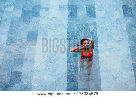 Enjoying vacation. Smiling beautiful young woman in swimming pool