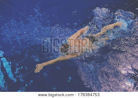 Male swimmer at the swimming pool. Underwater photo