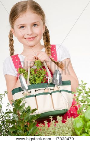 Little girl with gardening tools in herbal garden