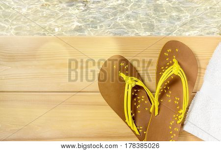 Summer beach vacation, flip flops and towel on wood deck with clear transparent sea water on background. Top view