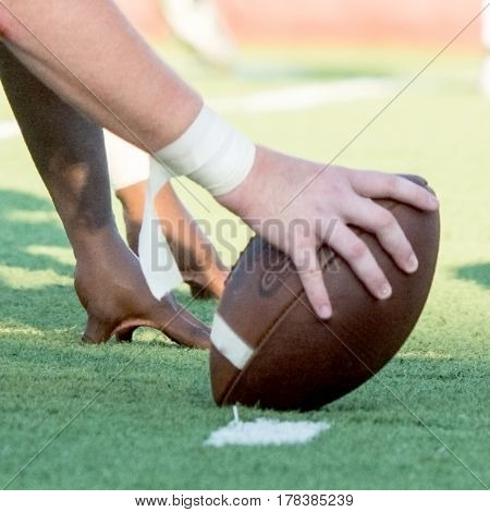 Close up of the hands of center and linemen before the play