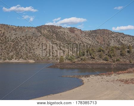 Prineville Reservoir in Central Oregon viewed from a cove with sandy shores hills rocks and juniper trees on a sunny spring day.