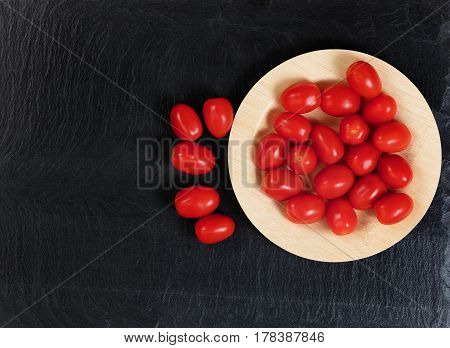 Overhead view of fresh cherry tomatoes on bamboo plate with black slate