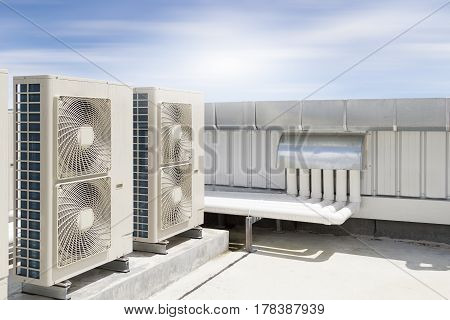 Air compressor machine part of air conditioner system on roof deck with sky background.