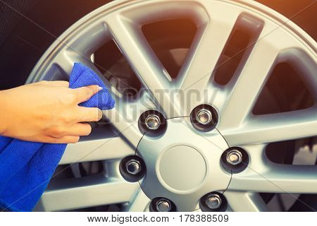 Women's hand wiping on alloy Wheels, vintage color tone.