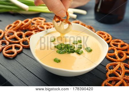 Female hand dipping pretzel in bowl with beer cheese dip, closeup