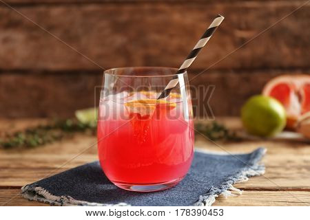 Refreshing cocktail with grapefruit on wooden table