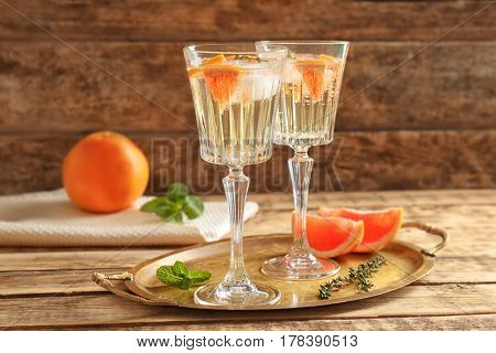 Tray with refreshing cocktails and grapefruit on wooden table