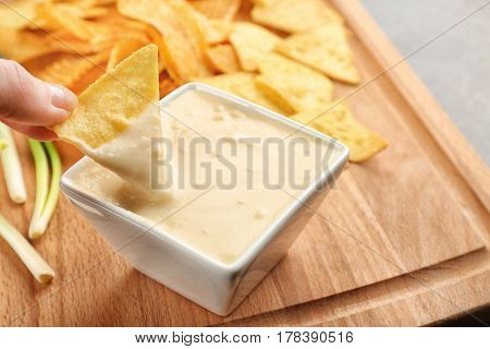 Female hand dipping nacho in bowl with beer cheese dip, closeup