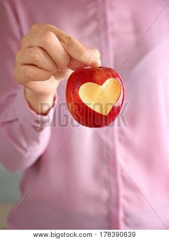 Woman hand holding fresh red apple with heart-shaped cut out, closeup