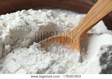 Wooden spoon in flour, closeup