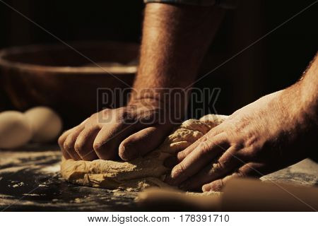 Hands of man kneading dough in kitchen, closeup