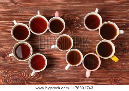 Delicious tea in cups forming spiral on wooden background