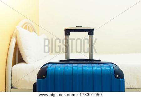 Blue bed and luggage in hotel room.