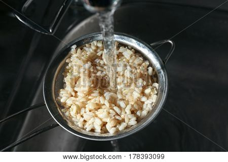 Washing brown rice with water in sieve