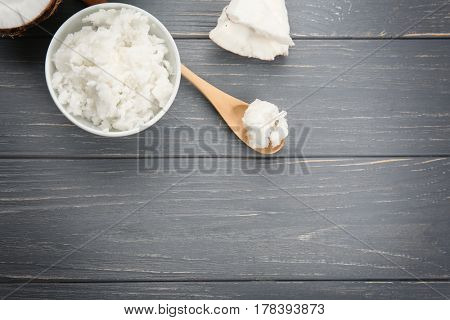 Bowl and spoon with fresh coconut oil on wooden grey background