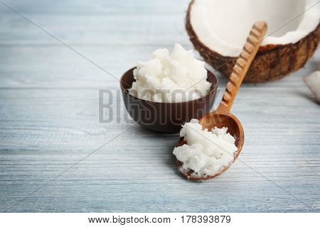 Decorative spoon and bowl with fresh coconut oil on light wooden background