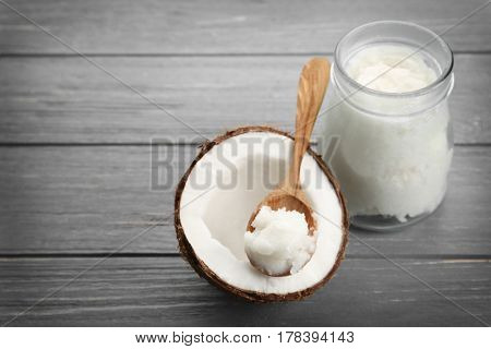 Coconut with spoon full of fresh oil on wooden grey background