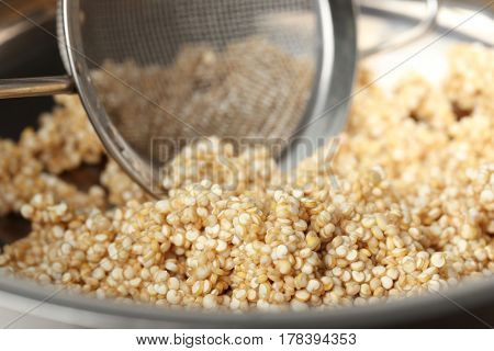 Quinoa seeds and sieve in saucepan, closeup