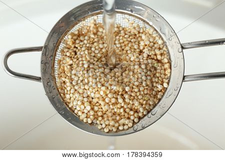 Washing quinoa seeds in sieve, closeup