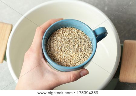 Female hand holding cup with quinoa seeds over saucepan