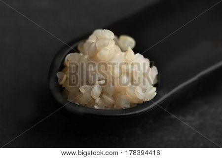 Measuring spoon with boiled sprouted organic white quinoa grains, closeup