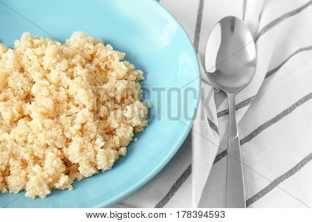 Blue plate with healthy quinoa porridge on table