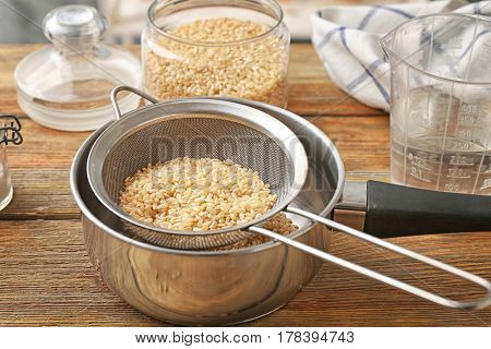 Sieve with raw brown rice in pan on wooden table